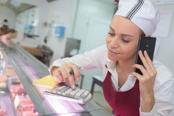 female butcher behind counter on the phone