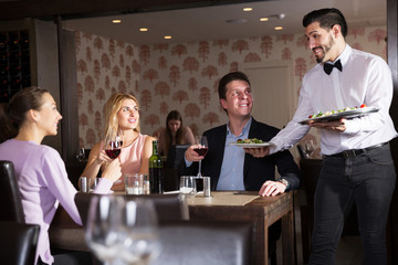 waiter bringing ordered dishes to guests