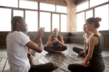 Excited african american man talking to sporty happy diverse friends sitting on mat in studio, happy black yoga instructor or life coach motivating young people having fun at seminar training class Wall mural