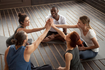 Diverse happy people giving high five sitting on mats at yoga seminar in studio, multiracial group joining hands celebrating good sport result, supporting motivation unity in fitness goal achievement