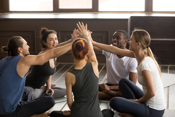 Diverse happy yogi people reach hands to give high five sitting on mats at yoga seminar training,...