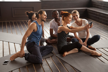 Smiling young multiracial people making selfie on smartphone before yoga training sitting on mats in studio, diverse sporty fit friends taking group self-portrait photo on phone after pilates class