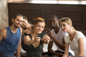 Attractive sporty smiling woman holding phone taking group selfie at training class in gym studio, diverse fit people, happy fitness friends or multiracial yoga team make self portrait on smartphone