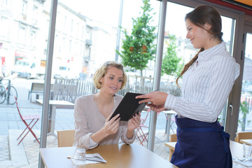 pretty young waitress takes order from female client