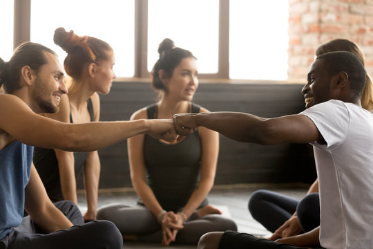 Smiling sporty fit african american and caucasian men fist bumping at group training meeting in gym studio, two diverse friends greeting or supporting team motivation for sport yoga teamwork concept