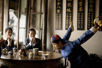 Young adult man performing a traditional tea ritual for business people at a cafe.
