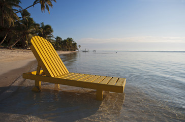 Yellow deck chair standing in shallow water on a tropical beach in the sunshine.