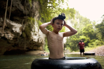 Young boy wearing a headlamp stands knee deep in water inside an inflatable ring.