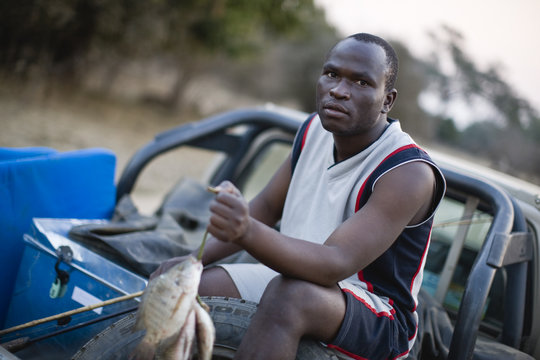 Portrait of a young adult man sitting in a truck holding fish.