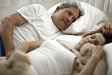 Sleeping couple sleeping with puppies.