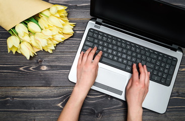 Top view of business woman hands typing on open laptop computer keyboard and bouquet of yellow tulips, copy space. Womens day, March 8. Business concept. Flat lay