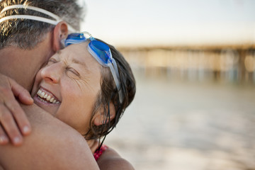 Mature couple wearing swimming goggles and hugging near lake