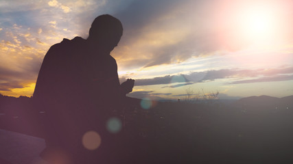 Silhouette of young muslim man praying during sunset