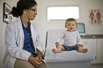 Doctor giving a baby boy a medical check up.