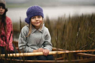 Young girl smiles slightly as she poses for a portrait while sitting in a wooden canoe among reeds on a lakeshore with her older sister sitting behind her.