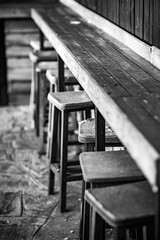 Very Old Weathered Wooden Chair Stools and Bench, Selective Focus on the most damaged one,  Black and White classic style photograph, Nostalgia for Old Photography