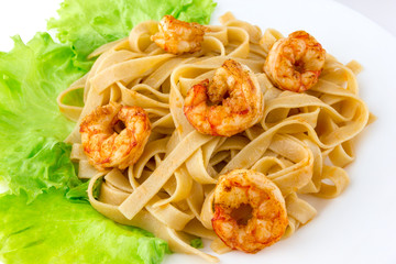 Boiled pasta with fried shrimp. Tagliatelle macaroni are observed with fried langoustines and lettuce leaves.
