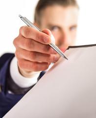 Businessman holds pen near paper document, close up.