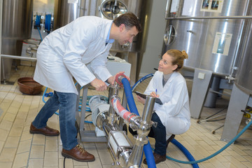 two workers in lab coats showing their dairy production process