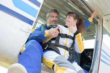 Man and woman giving thumbs up before skydiving