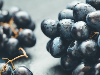 Close-up of a wet branch of the blue grape on black stone board.