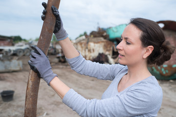 female working with old metal bars at a scrapyard