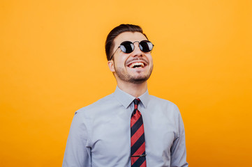 Happy smiling young man with sunglasses over yellow background.