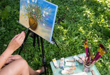 The artist paints a painting with oil on the nature.