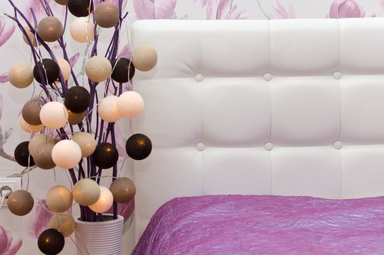 Cotton light balls string in brown, beige and white colors in beautiful pink bedroom interior with stylish bed and decorative vase.