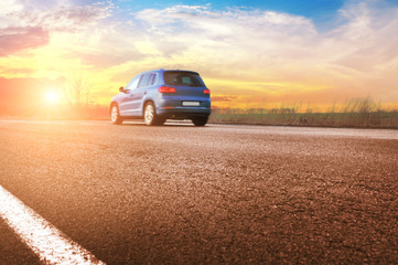 Printed roller blinds Blue sky A blue car on the countryside road against night sky with sunset