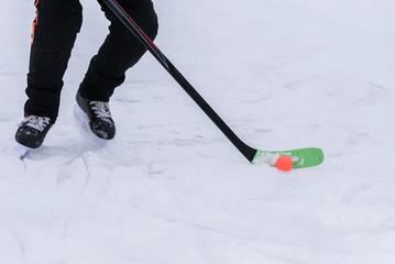 man playing hockey with an orange ball