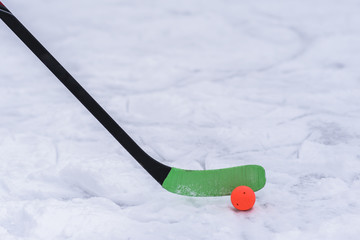 close-up of a hockey stick with an orange ball