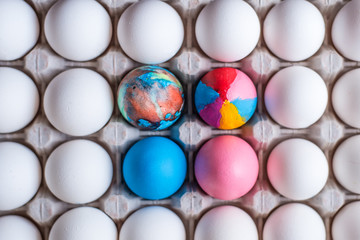 Colorful eggs and a cardboard box with white eggs