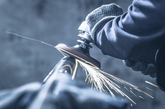 Metal polishing with a hand sander with a polishing disk. Toned image.