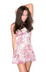 Modèle féminin souriant posant debout avec une robe fraîche à fleurs, été, printemps, Magazine Mode Fond blanc Studio
