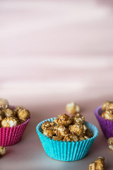 Sweet caramel popcorn in colorful cups with copy space .