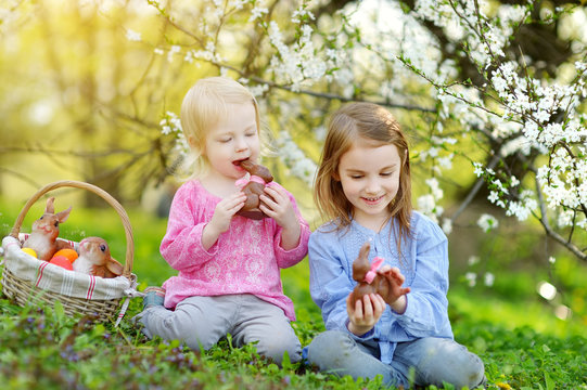 Two adorable little sisters eating chocolate bunnies in a spring garden on Easter day