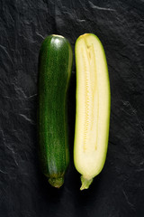 Green zucchini cut in half on a black background, top view
