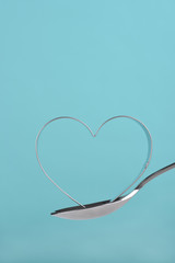 Heart shaped cookie cutter balanced on a spoon