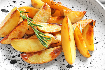 Plate with delicious baked potato wedges, closeup