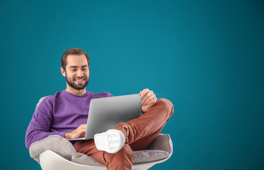Handsome man with laptop sitting in comfortable armchair against color wall