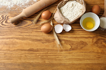 Wheat flour, eggs and kitchen utensils on wooden background