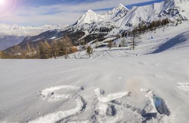 Ski written on fresh powder snow with Alps background