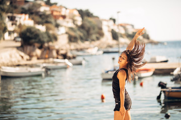 Sensual carefree summer woman enjoying vacation.Seaside stress less lifestyle.Fit traveler enjoying life.Full of energy.Energetic active enthusiastic female.Throwing hair,cheerful sun loving person