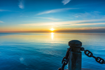 Beautiful blue and yellow sunrise with sun rays shining above horizon, marine post