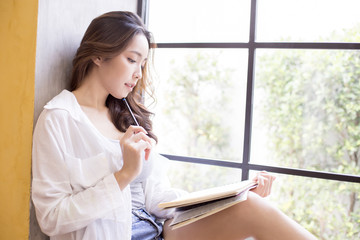 Asian woman thinking how to draw picture in book. People with education concept.