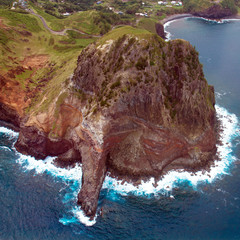 Large, dramatic rock surrounded by surf on the coast of the island of Maui in Hawaii, aerial shot from a small, low-flying prop plane