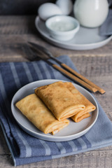 Russian Puncake Crepes stuffed with mushrooms and mozzarella on wooden table background.