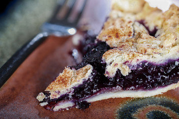 Close up of a slice of blueberry pie with fork