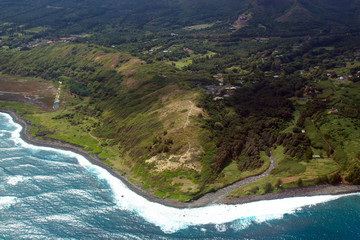 Aerial view of the island of Maui's coastline, waves, and surf in Hawaii, shot from a small, low-flying prop plane